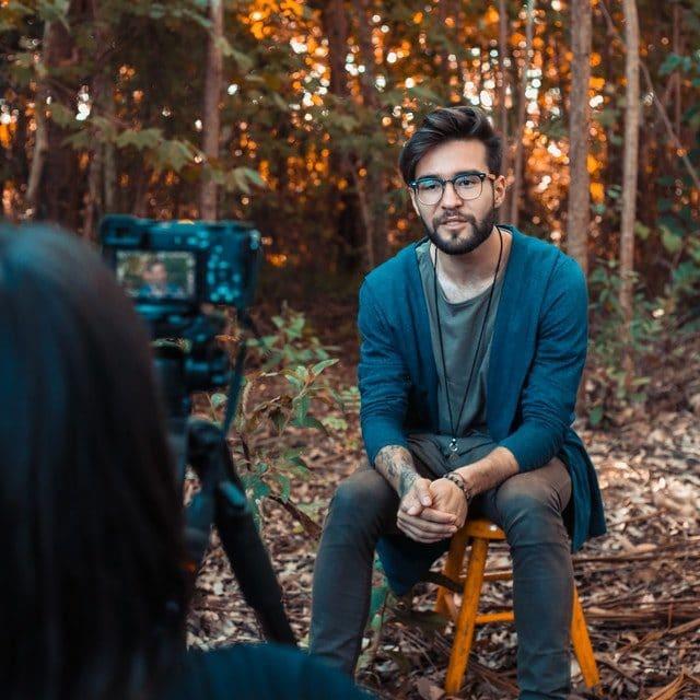 homme assis sur une chaise dans un bois enregistrant une vidéo